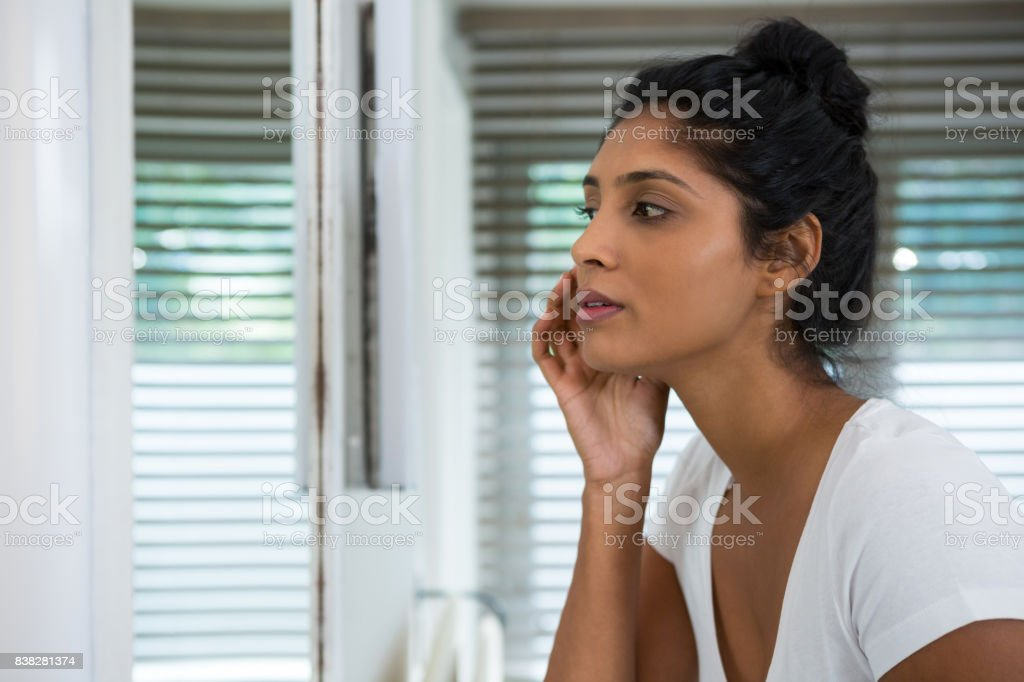 Woman touching face in bathroom stock photo