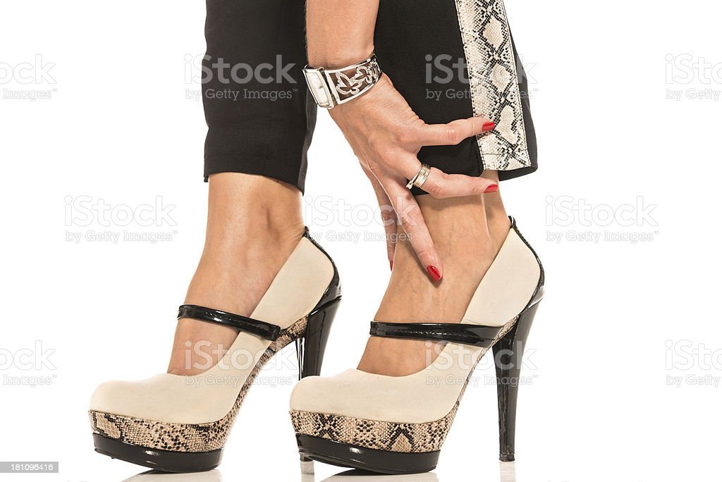 A woman touching her ankle wearing high heel shoes royalty-free stock photo