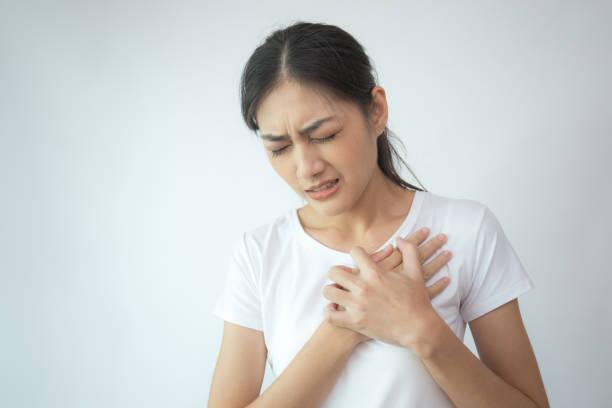 Frau Brust mit Händen zu berühren. Junge asiatische Frau fühle den Schmerz in der Brust. Isoliert auf weißem Hintergrund. – Foto