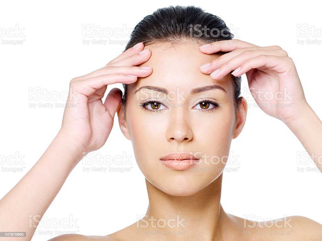 Woman touching her forehead without wrinkle stock photo