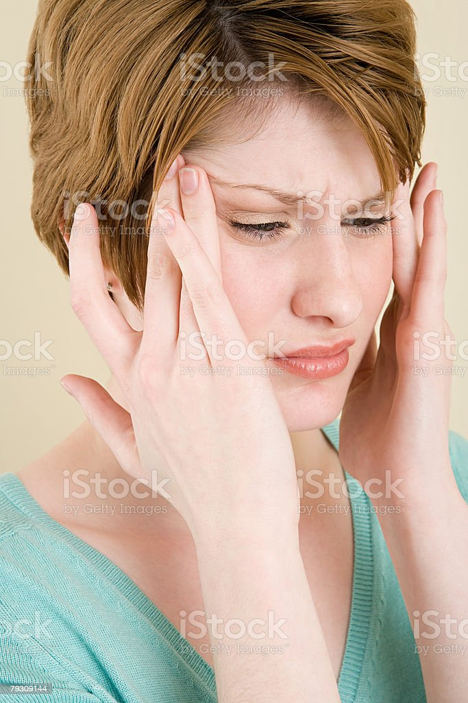 A woman touching her head royalty-free stock photo