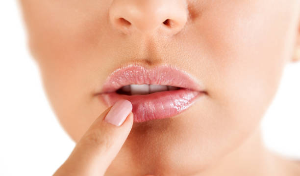 Woman touching her lips with herpes herpes on the lips, part of a woman's face with finger on lips with herpes, beauty concept herpes stock pictures, royalty-free photos & images