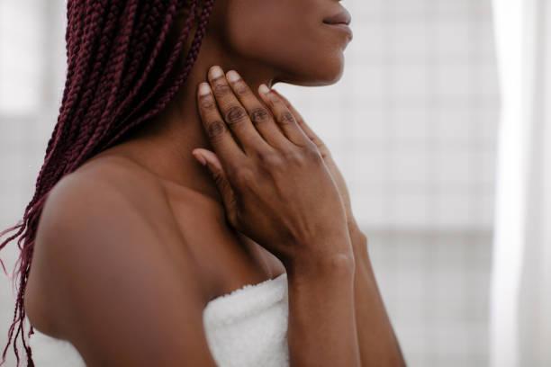 een vrouw die haar nek aanraakt - nek stockfoto's en -beelden