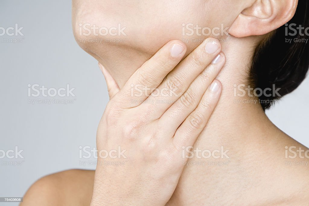Woman touching her neck stock photo
