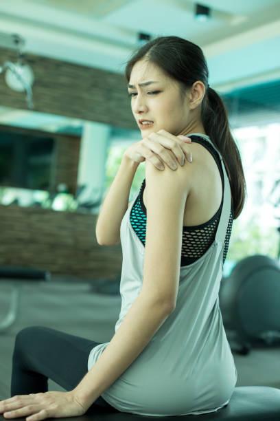 Frau, die ihren Hals mit Hände während der Übung zu berühren. Junge asiatische Frau Schmerzen im Nacken. – Foto