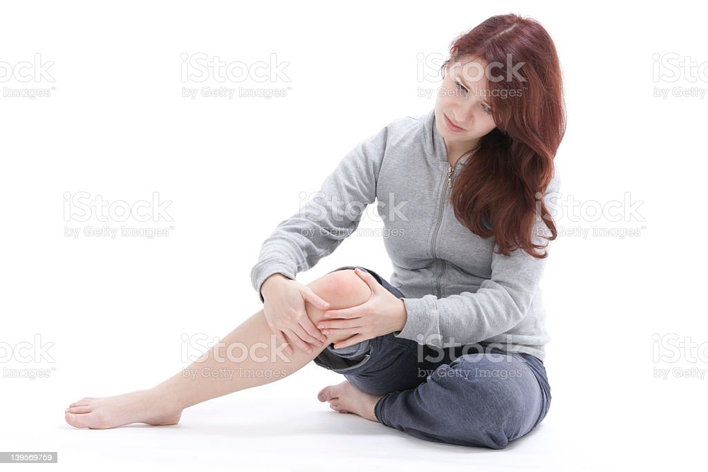 A woman touching her painful knee  stock photo