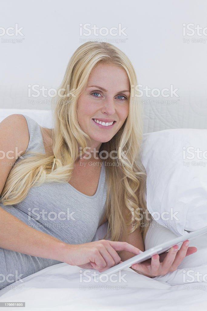 Mujer tocando su tableta en la cama foto de stock libre de derechos