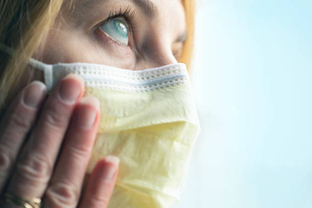 Woman Touching Her Virus Protection Face Mask stock photo