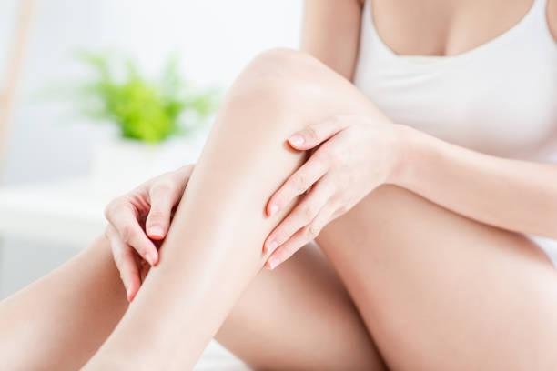 完璧な剃毛脚に触れる女性 - 脛 ストックフォトと画像