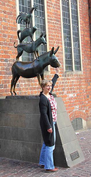 frau berühren statue der stadt musicians_bremen - die brüder grimm stock-fotos und bilder