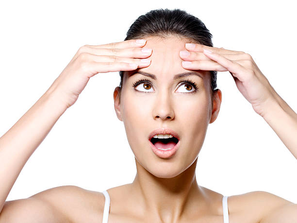 Woman touching the  creases  on forehead stock photo