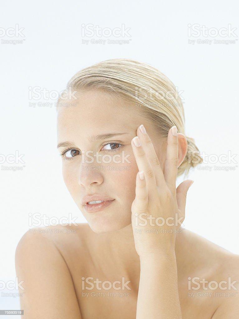 Mulher a tocar na face lateral do seu foto de stock royalty-free