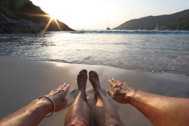 pov frau berühren zehen am strand - armband water stock-fotos und bilder