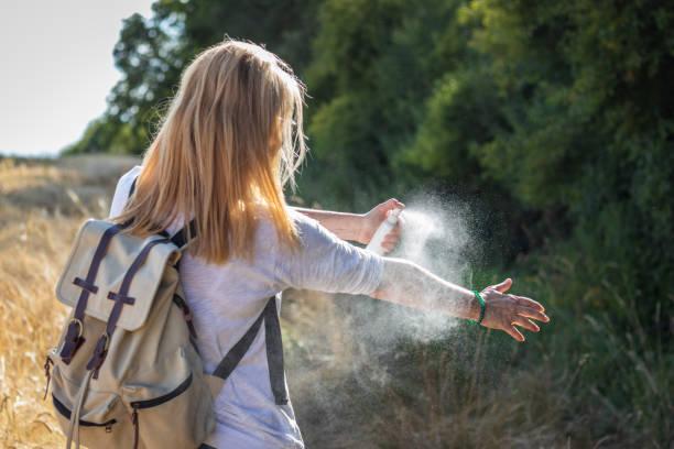 touristin, die bei einer wanderung in der natur mückenschutzmittel auf die hand bringt. insektenbekämpfungsmittel. - zeckenmittel stock-fotos und bilder