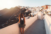 istock Woman tourist enjoying the view of Fira village, Santorini 1280501183