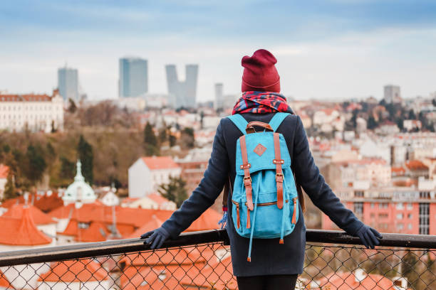 woman tourist in a coat with a backpack travels in the city park of prague, rear view - portugal map imagens e fotografias de stock