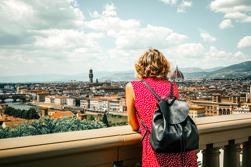 Woman tourist in red admires Florence Firenze (Duomo, Arno River, towers, cathedrals, tiled roofs of houses) from Piazzale Michelangelo, cityscape panorama top view, Florence, Tuscany, Italy