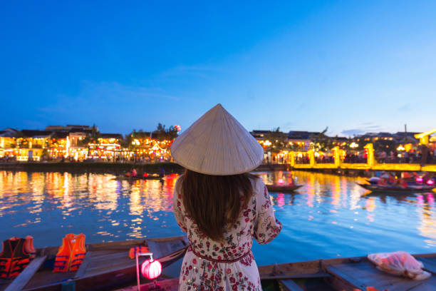 Woman tourist is sightseeing at Thu Bon riverside and wearing Non La (Vietnamese Hat) in Hoi An, Vietnam. stock photo