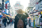 Woman tourist is traveling into Hongdae fashion street market in Seoul, Korea.