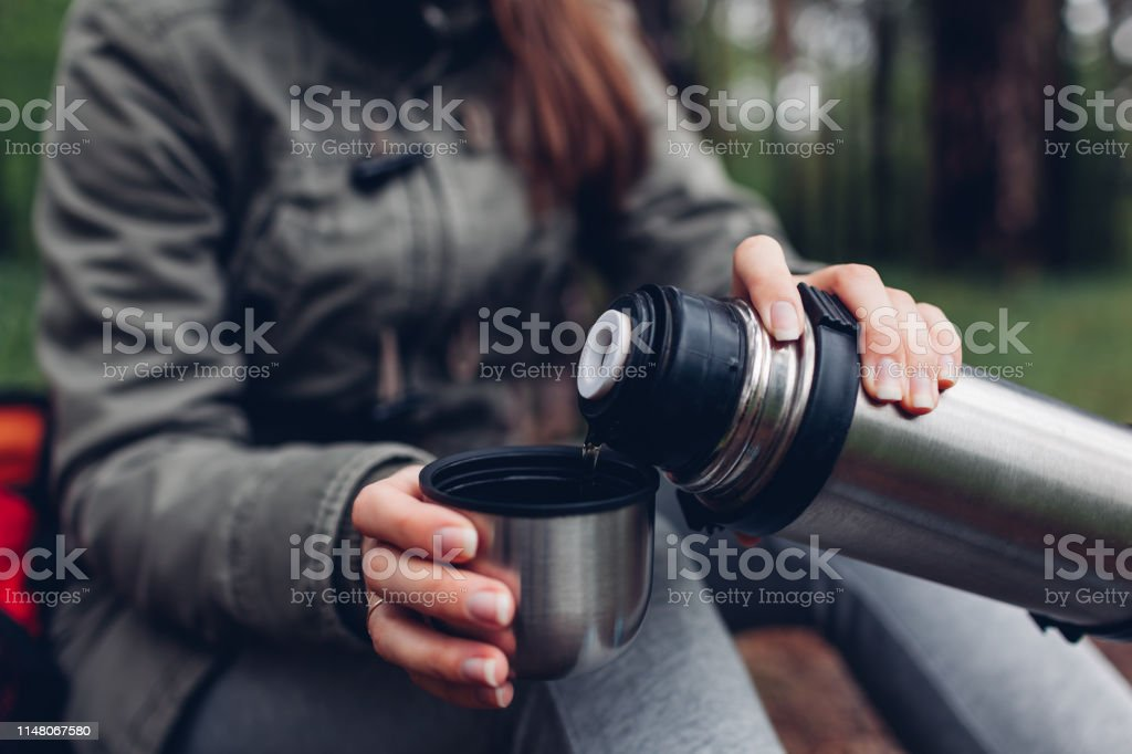 Woman tourist pours hot tea out of thermos in spring forest. Camping,...