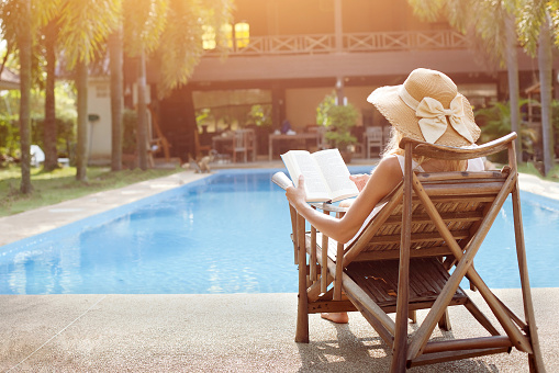 relaxation concept, woman reading book near swimming pool of hotel