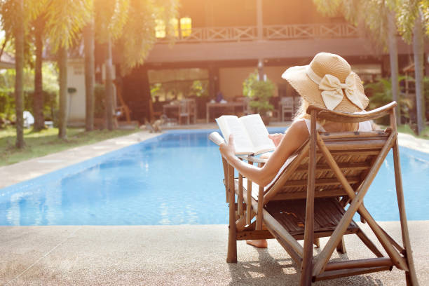 woman tourist relaxing near luxury swimming pool in hotel stock photo
