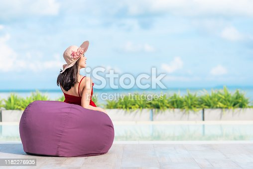 883117662 istock photo woman tourist relaxing on bean bag by the pool in hotel 1182276935