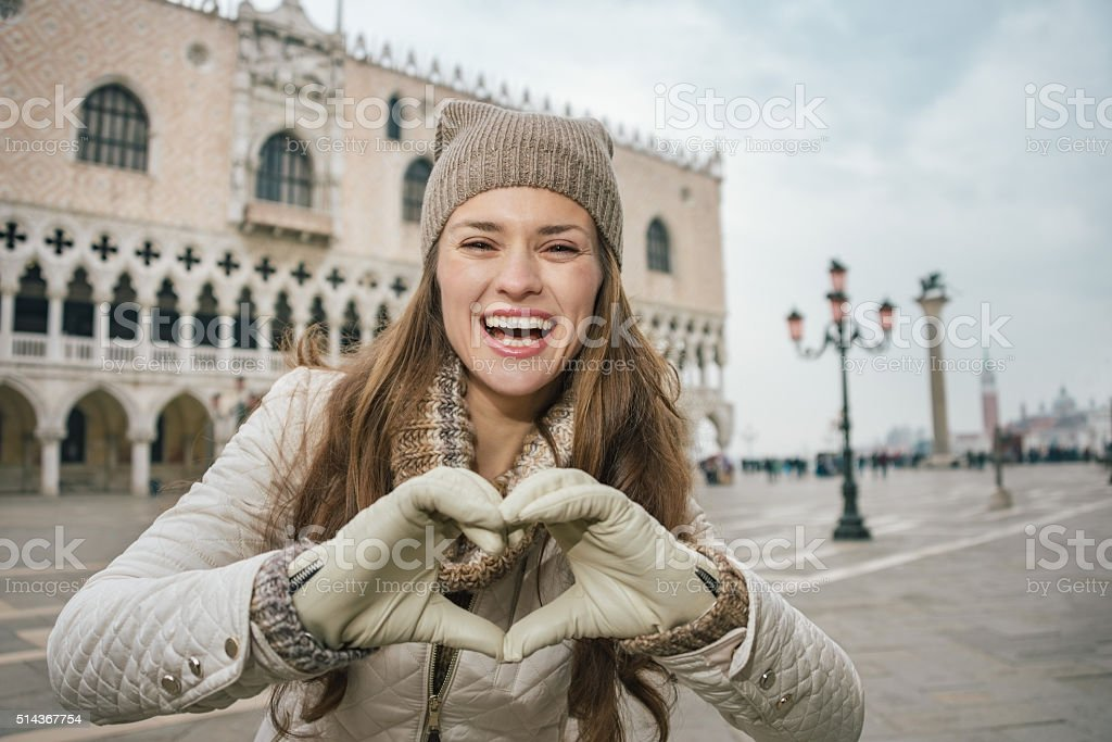 Woman tourist showing heart shaped hands on St. Mark's Square stock photo