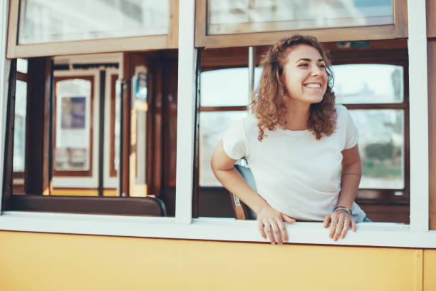 woman tourist taking a ride on the old vintage bus in foreign country - femme portugal photos et images de collection