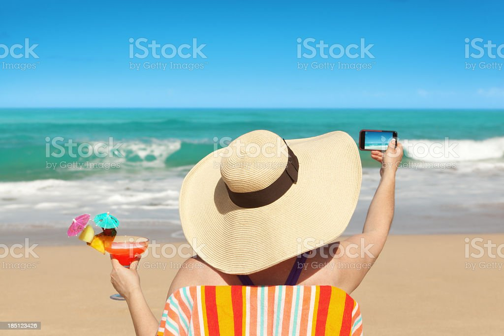 Woman Tourist Taking Beach Photo with Smartphone on Summer Vacation royalty-free stock photo
