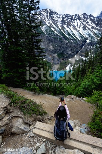 A Tourist taking picture with mobile phone half way between Lake Louise and Lake Agnes, Banff National Park
