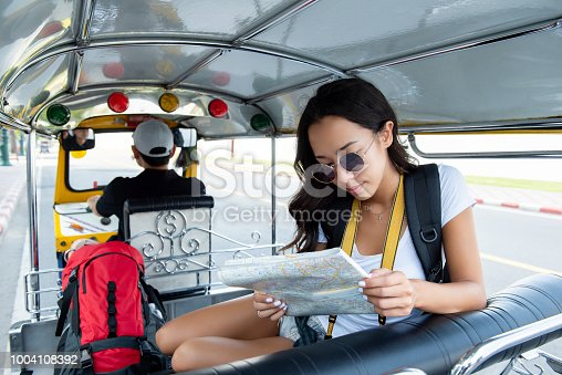 Young independent woman tourist traveling on local Tuk Tuk taxi exploring the city in Bangkok Thailand on summer vacations