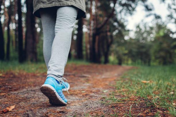 vrouw toerist wandelen in het voorjaar bos. close-up van schoenen. reizen en toerisme concept - wandelen stockfoto's en -beelden