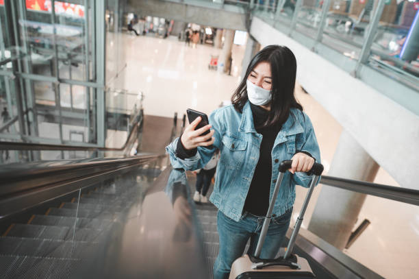 woman tourist wearing mask with luggage using smartphone mobile on escalator stock photo