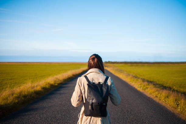 frau tourist mit rucksack unterwegs hintergrund. in richtung zum ziel - neue abenteuer stock-fotos und bilder