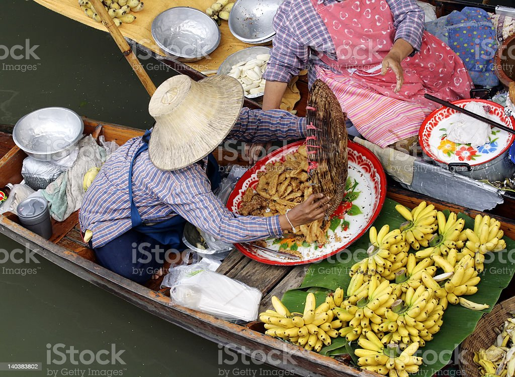 Woman Trading Food at One of Thailand's Floating Markets. stock photo