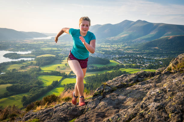 Woman trail runner bounding up rocky mountain summer summit stock photo