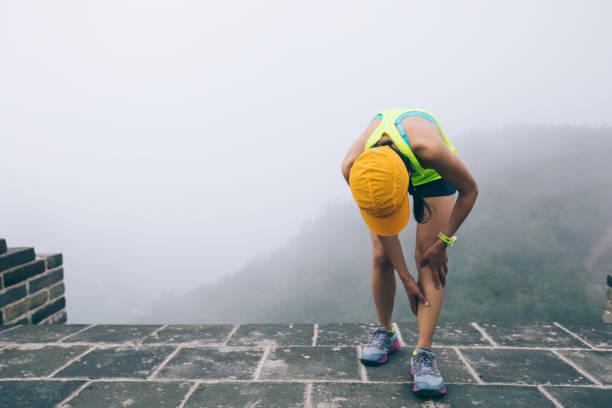 女性トレイルランナーは、山の頂上で彼女のスポーツ負傷脚を保持します - 脛 ストックフォトと画像