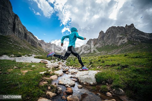 istock Woman trail runner jumping over samll river on beautiful mountains 1042103998