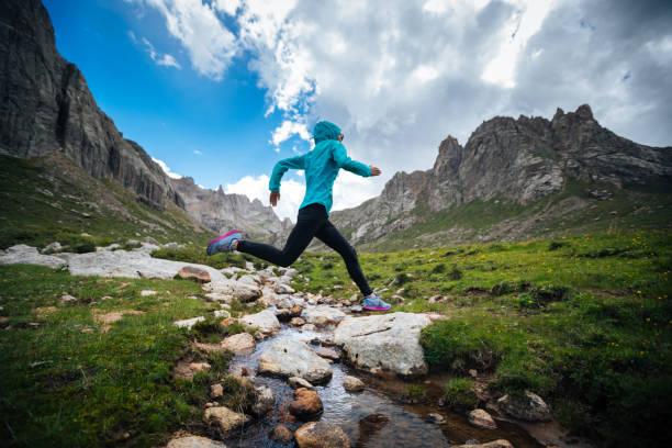 美しい山々 に samll 川を飛び越えて女性トレイル ランナー - ジャケット ストックフォトと画像