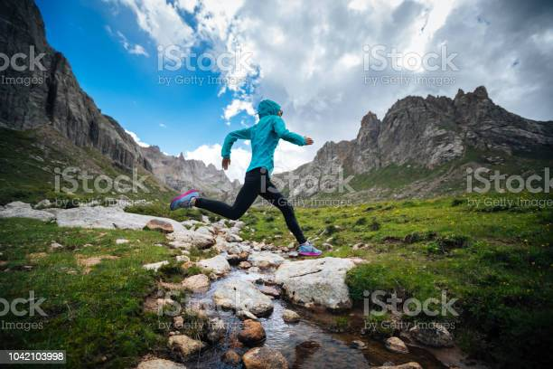 Photo of Woman trail runner jumping over samll river on beautiful mountains