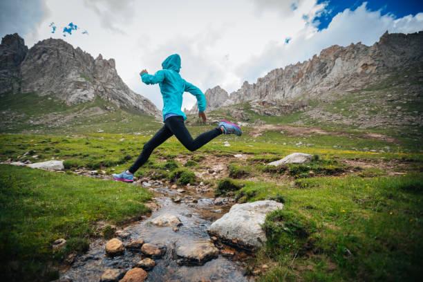 Frau Trailläufer springen über Samll Fluss auf Berge – Foto