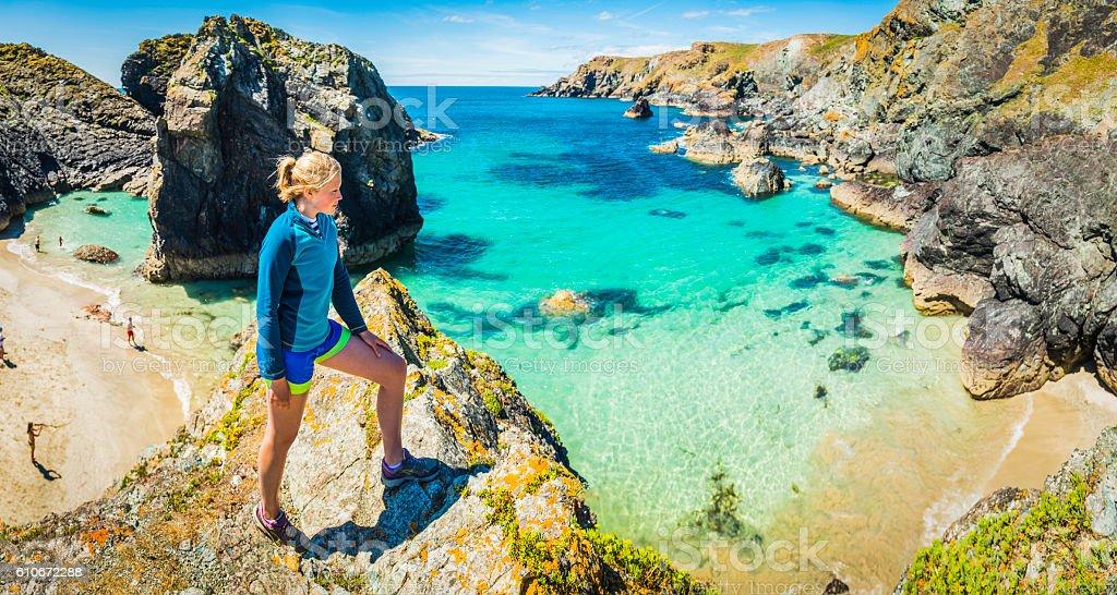 Woman trail runner overlooking idyllic ocean beach bay cliffs panorama stock photo