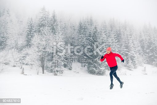 484750230 istock photo Woman trail running on snow in winter mountains 924837610