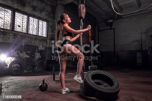 istock woman train with a hammer and tires in an old garage 1162000249