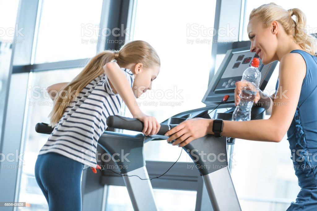 Woman trainer looking at small girl workout on treadmill royalty-free stock photo