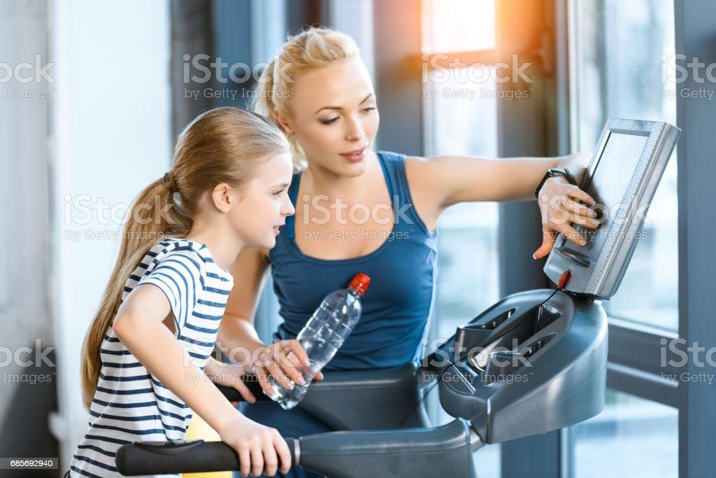 女性教練與小女孩鍛煉在跑步機 免版稅 stock photo