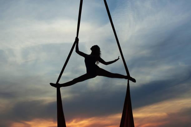 frau training akrobatik in der luft. - trapez stock-fotos und bilder