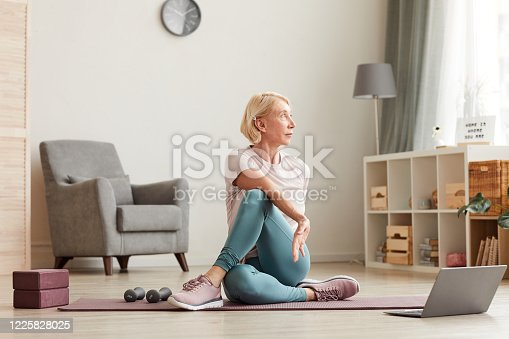 Senior woman sitting on the floor on exercise mat in front of laptop and training at home