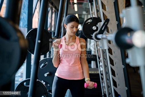 Latin American woman training at the gym using free-weights – fitness concepts